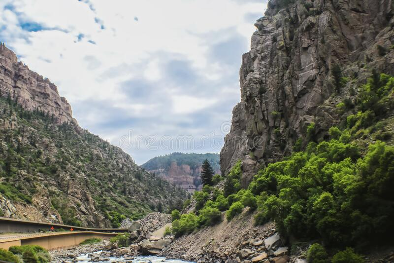 Stream beside built up highway through towering cliffs of Rocky Mountains royalty free stock photo