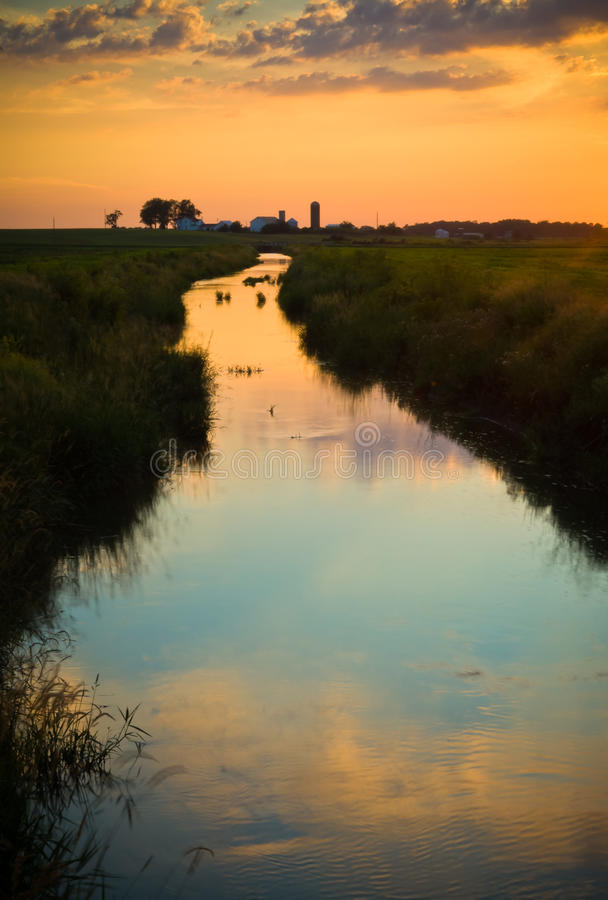 Stream In the Country. A view of a stream that divides a field while providing irrigational watering for the farm it leads in the distance under a warm and royalty free stock images