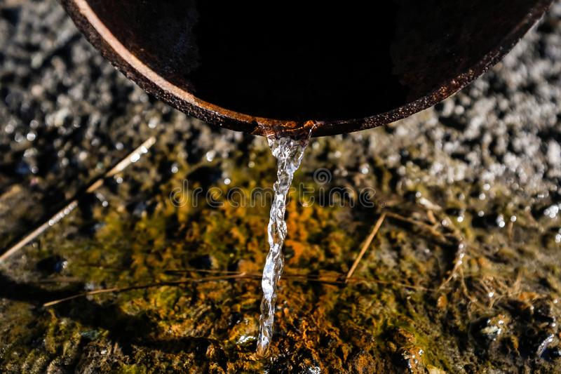 A stream of crystal clear water flows, falling from the drain pipe to the ground and sidewalk. Rain water flowing out of the royalty free stock photos