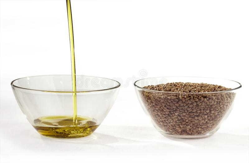 A stream of flowing hemp seed oil and hemp seeds in a round glass bowls. On a white background stock images