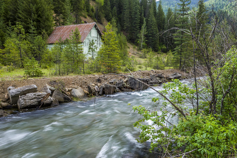 Stream flows by old barn. royalty free stock photos