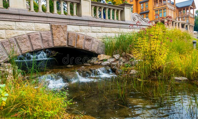 A stream flows from under a massive brick bridge.  stock photography