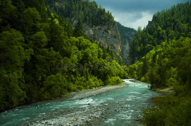 Stream and  forests in DaYu valley national park. Under dark clouds stock photography
