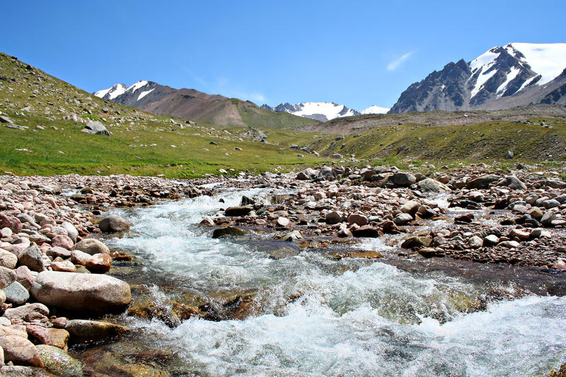 Stream of mountain river in North Tien-Shan. Against blue sky stock images