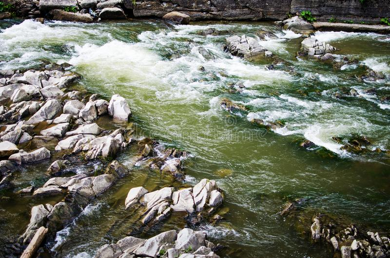 A stream in the mountains flows along the rocks and a stormy waterfall royalty free stock photography