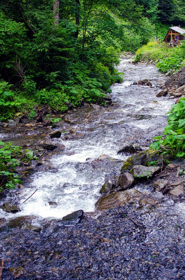 A stream in the mountains flows along the rocks and a stormy waterfall stock photos