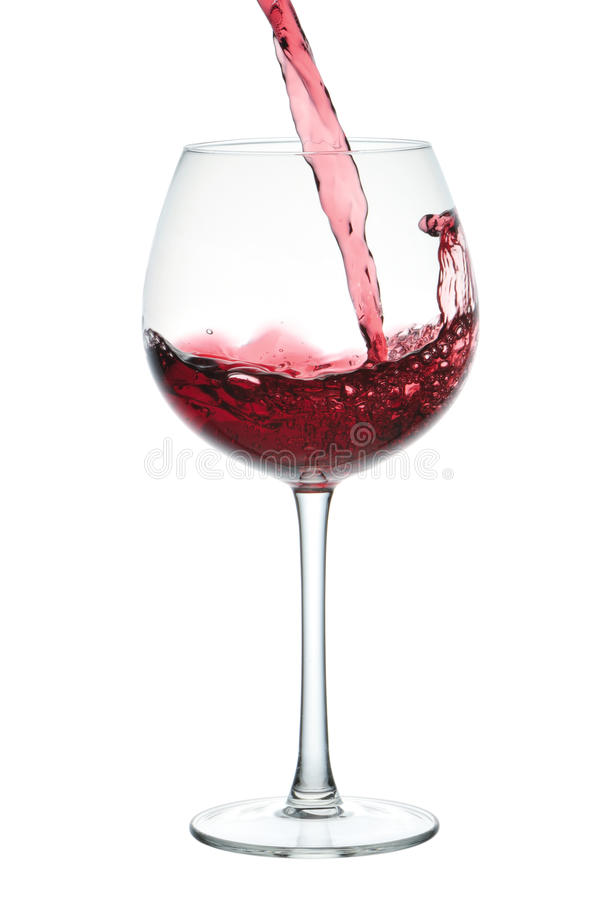 Stream of red wine falling in goblet. Isolated on white stock image