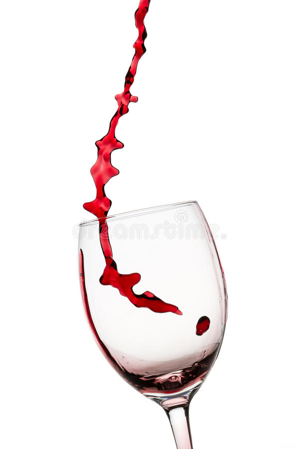 Stream of red wine pouring into glass stock images