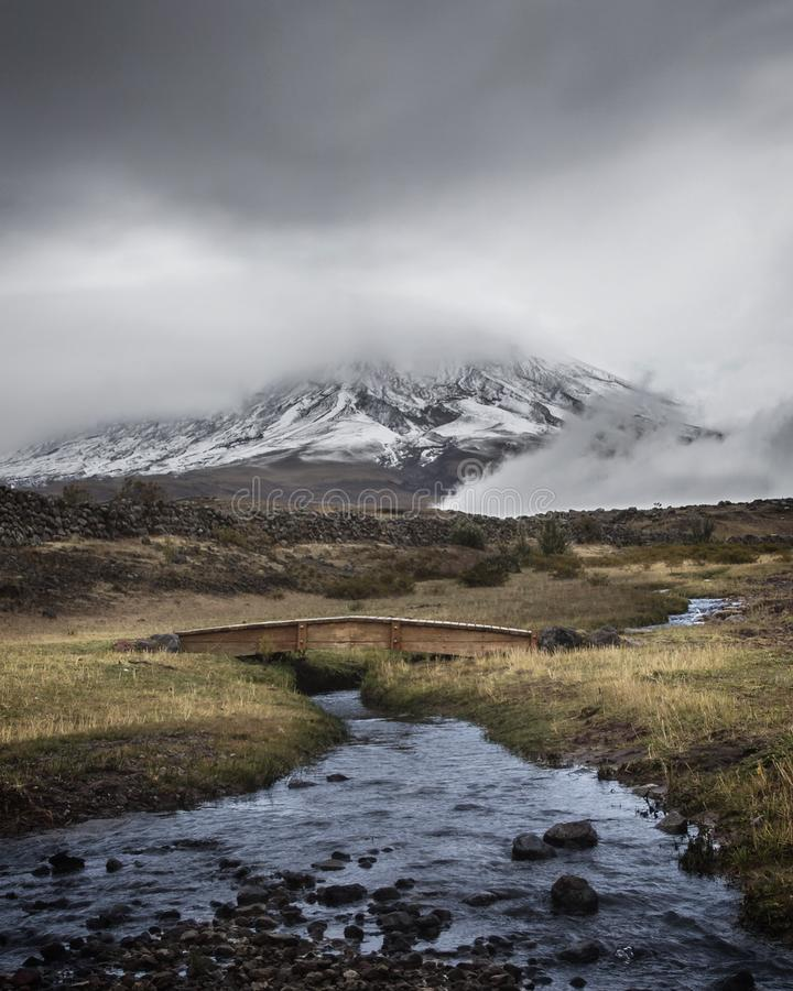 Stream Running Under Small Bridge in front of Cotopaxi Volcano on a Stormy Day royalty free stock image