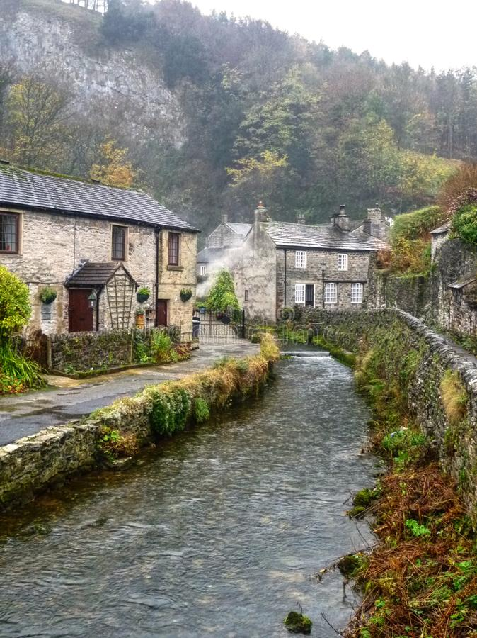 Stream runs between the pretty village cottages of Castleton, Derbyshire Peak district. Peakshole water is the stream that runs from Peak cavern, through the stock image