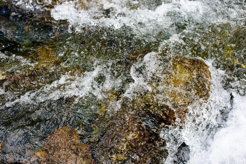 The stream slapped the waves on the stone stock images