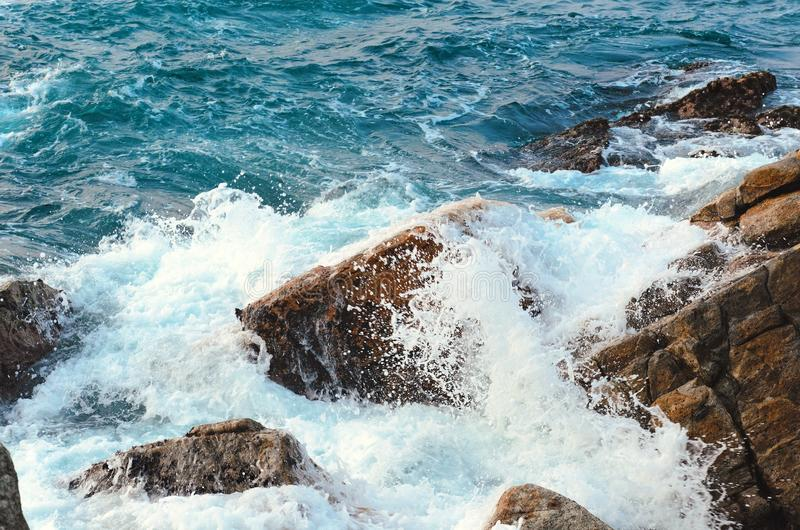 Stream of water crashes at rocky beach, raging sea. Sea water with foam, wave and beach. stock photography