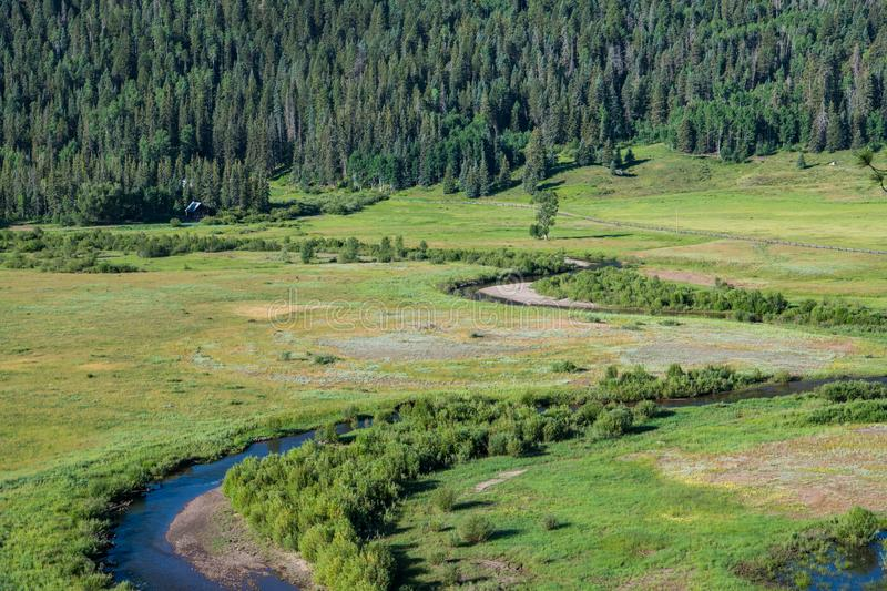 A stream winds through a valley beneath a forest of spruce and pine trees. A river curves through a grassy valley and ranch near Pagosa Springs, Colorado stock images