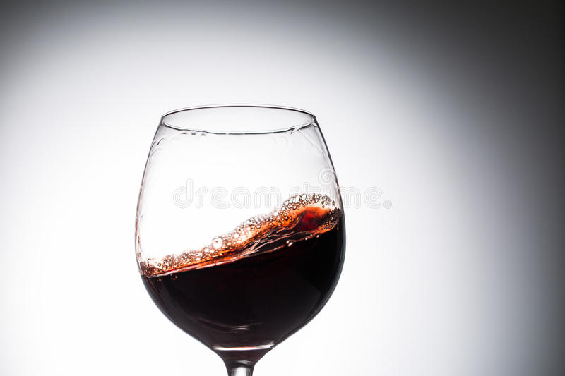 Stream of wine being pouring into a glass. Closeup splash of wine stock images