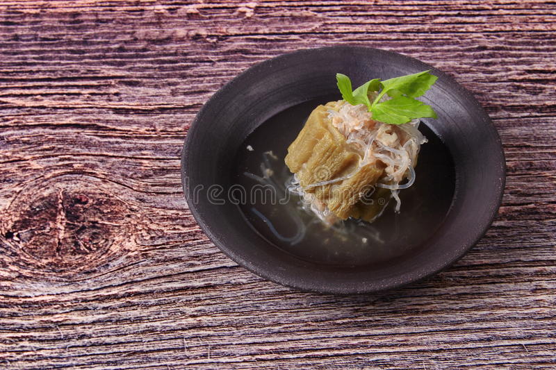 Streamed gourd wrap vermicelli and minced pork in soup. Streamed gourd wrap vermicelli and minced pork in bone soup in black dish on wood royalty free stock image