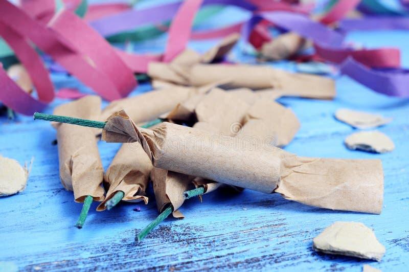 Streamers, confetti i petardy na nieociosanym błękitnym drewnianym sura, zdjęcie stock