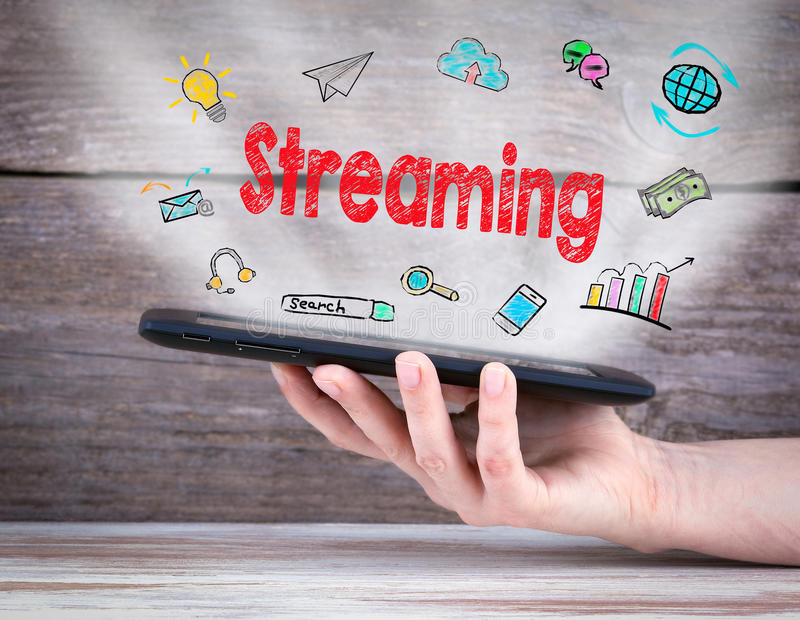 Streaming concept. Tablet computer in the hand. Old wooden background royalty free stock image