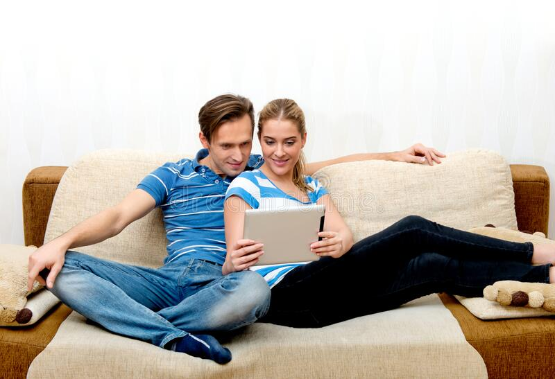 Streaming media - movie on tablet. Couple enjoying of watching streaming media on tablet while sitting on sofa stock images