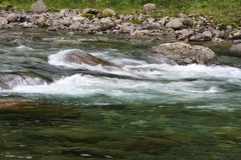 Streaming water in the river with rocks stock photography