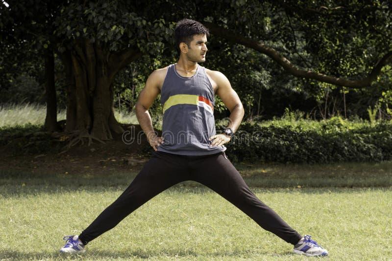 streching他的在运动场的运动年轻人腿 健康生活方式、健身和体育概念 库存图片
