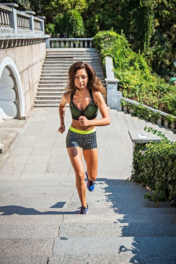 streching和做锻炼的活跃少妇在公园 训练户外在保加利亚的适合的女性体育模型女孩 图库摄影
