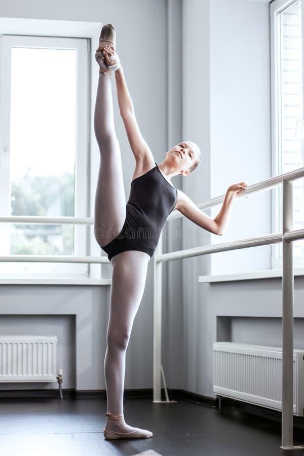 streching她的腿的年轻芭蕾舞女演员 库存照片
