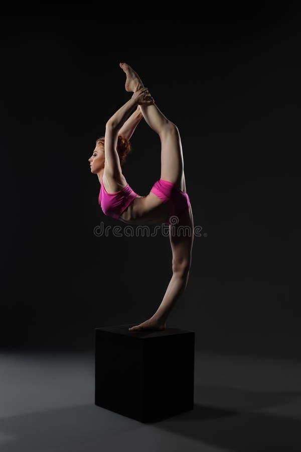 streching苗条停留在立方体的俏丽的体操运动员 免版税库存图片