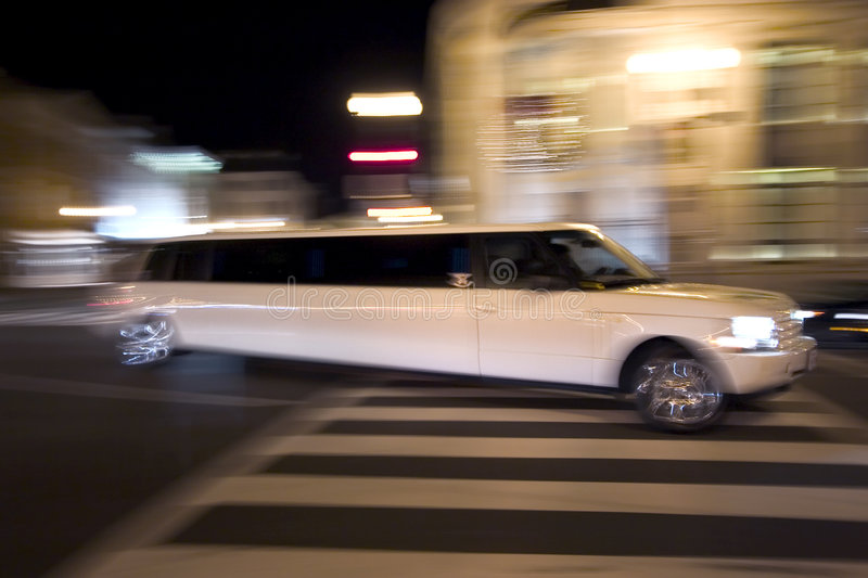 Streeeeeetch car in motion. Limousine at night in motion royalty free stock photography