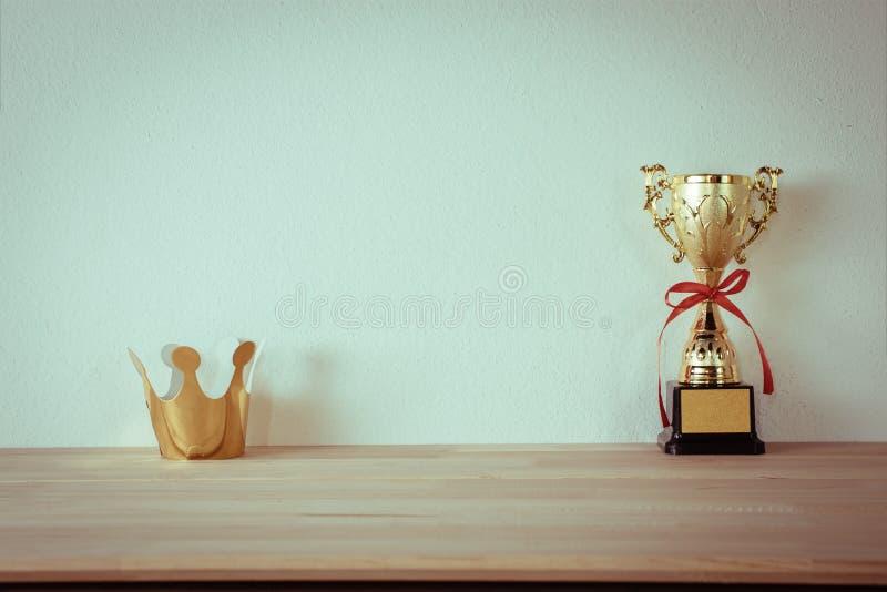Streeft de karton gouden kroon met kampioens gouden die trofee wordt geplaatst op na stock afbeeldingen