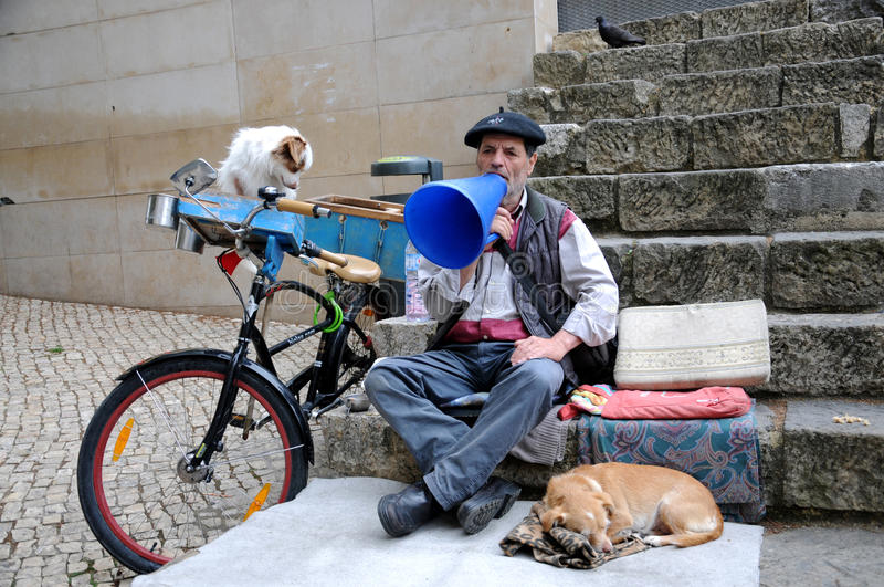 Street actor. Man singing in order to earn a little money for himself and his two dogs. So that you can hear him very loud, he sings through a selfmade