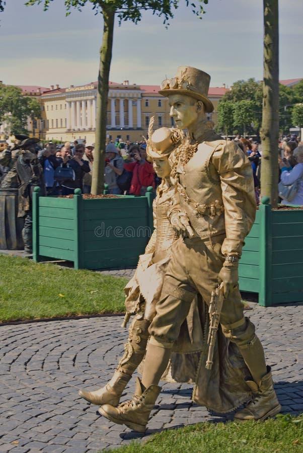 Street actors in golden costumes walk on Dvortsovaya Square in Saint-Petersburg royalty free stock image