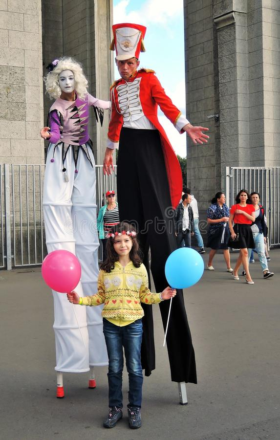 Street actors walk on stilts and pose for photos in Moscow. MOSCOW - AUGUST 01, 2015: Street actors walk on stilts and pose for photos in VDNH park in Moscow royalty free stock photo