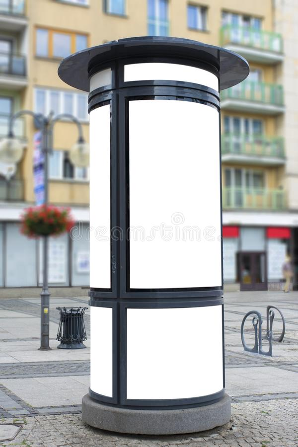Street advertising column stand on sidewalk stock image