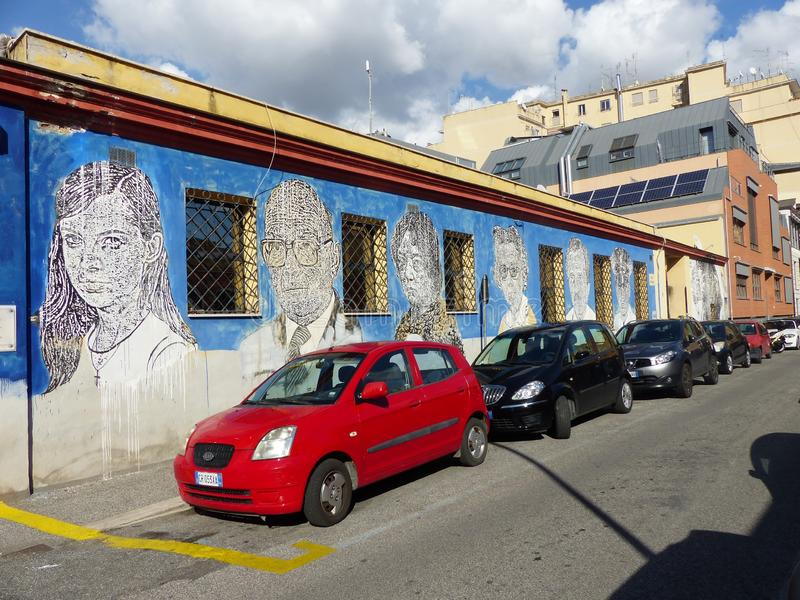 Street art of faces of ordinary people on a blue wall of a low building of the Ostiense district of Rome in Italy. stock images