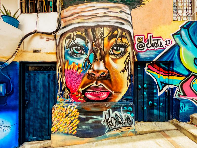 Street art graffiti on a wall in the street of Medellin, Colombia. Medellin, Colombia - March 28, 2018: Street art graffiti on a wall in area called Comuna 13 royalty free stock photography