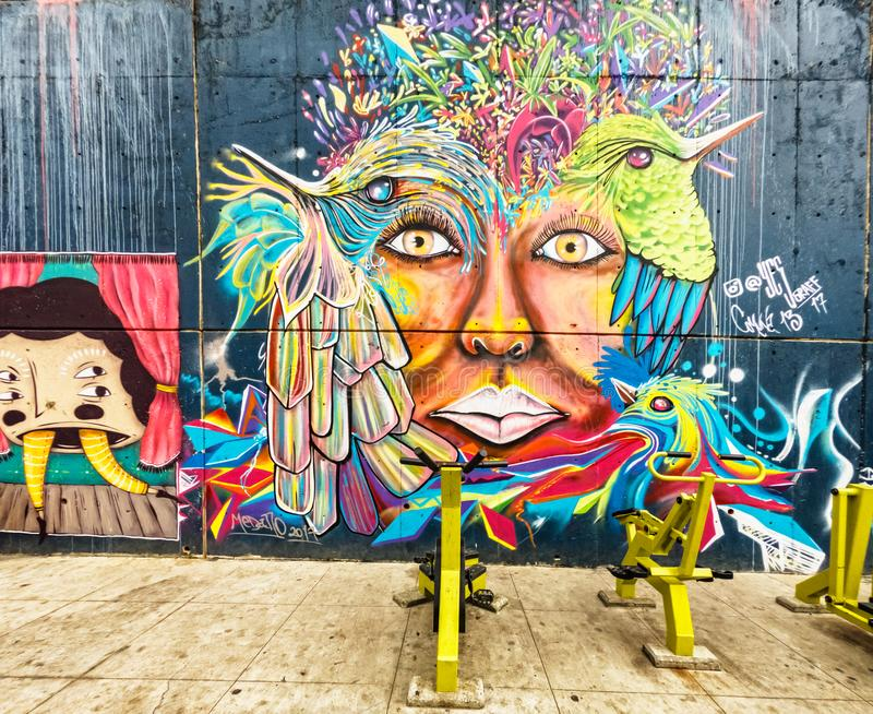 Street art graffiti on a wall in the street of Medellin, Colombia. Medellin, Colombia - March 28, 2018: Street art graffiti on a wall in area called Comuna 13 stock photography