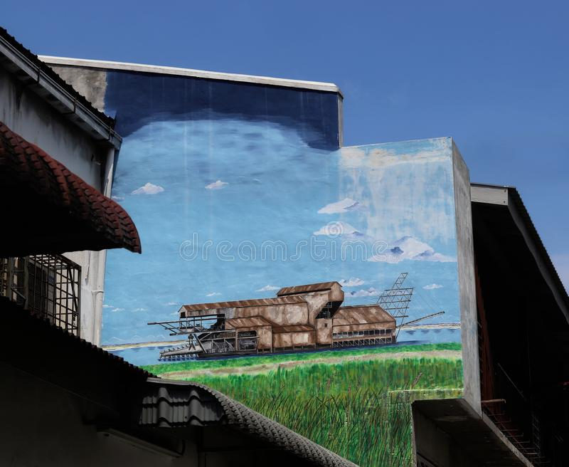 Street Art - Mural Of A Tin Dredge. Wall painting of an old tin dredge at a shophouse in Ipoh, Malaysia stock photography