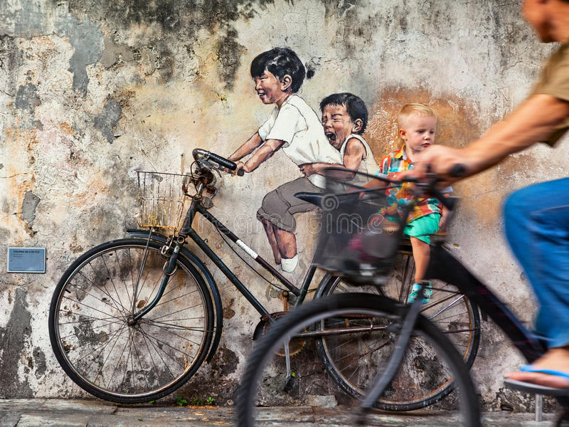 Street art object children on bicycle in Georgetown Penang. Georgetown, Penang, Malaysia - March 02, 2016: Cycling man look at little child siting on bicycle stock image
