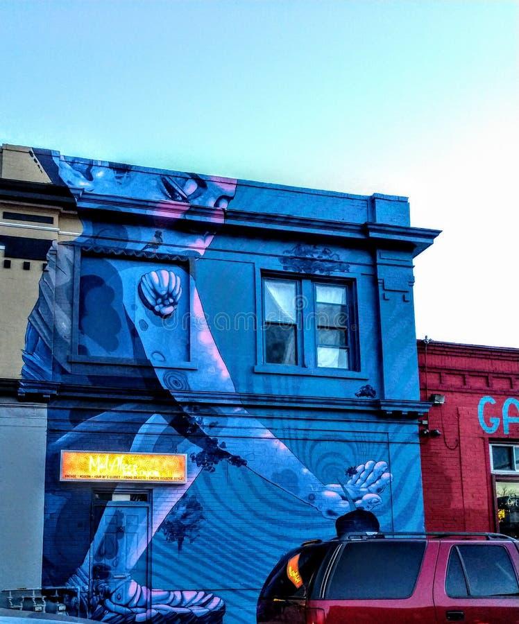 Street art. Powerful or peaceful? Blue girl street art royalty free stock photo