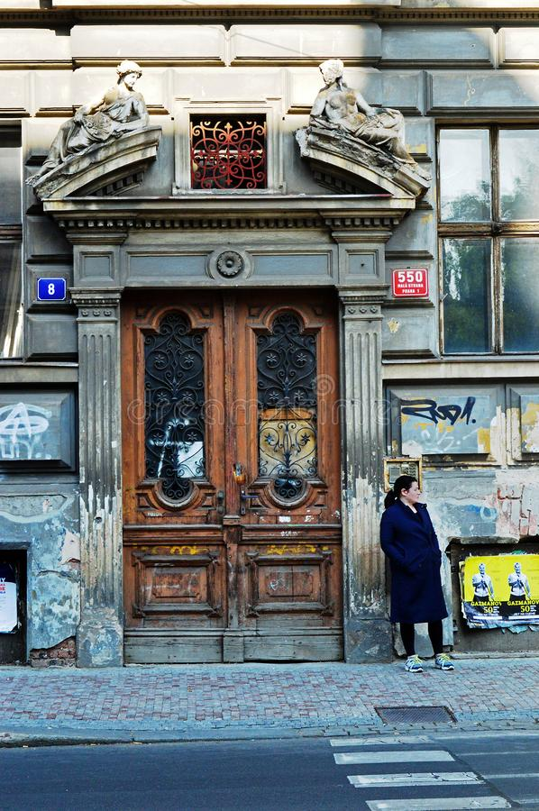 Portrait view - Street art - woman waiting outside grand old building covered in grafitti prague czech republic royalty free stock photo