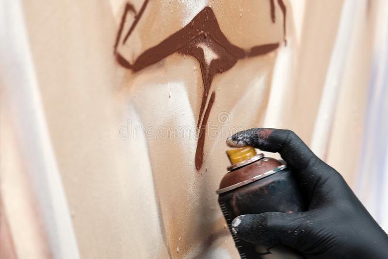 A street artist in black gloves draws an abstract image using a brown spray paint. Graffiti concept. Close-up of a hand with a bal stock photo