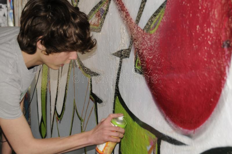 Street artist busy with an aerosol can. Bare wall in London`s Undercroft skateboard Park is decorated with graffiti by a street artist stock photos