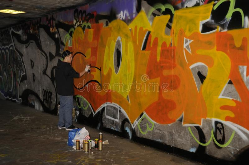 Street artist busy creating a graffiti. Street artist decorating a wall of the Undercroft in London, UK stock photos