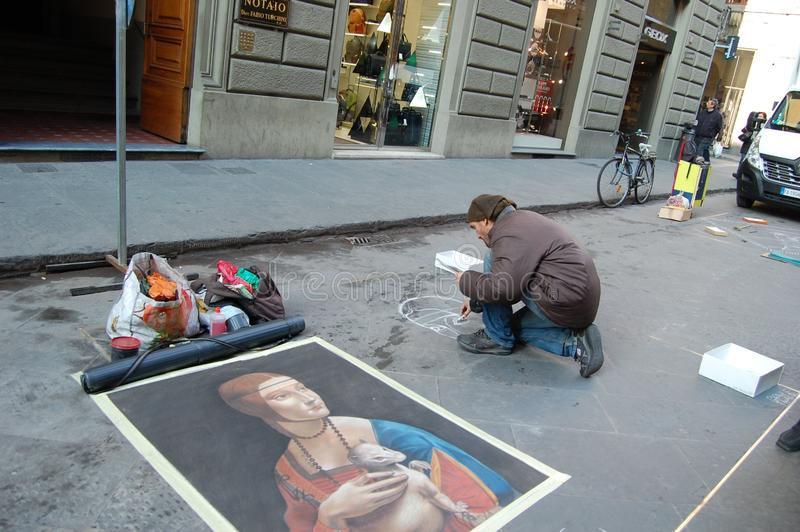Street artist draws on the asphalt portrait of a lady with an ermine. royalty free stock image