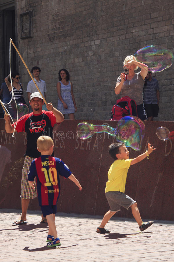 Street artist entertain children with bubbles with bubbles. Street artist entertain children on square a front of Basilica del Santa Maria del Mar, Barcelona stock images