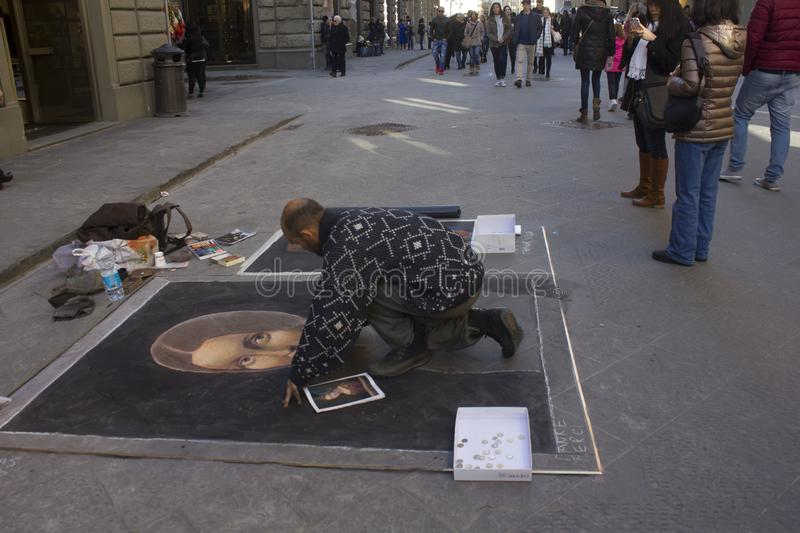 Street artist in Florence, making art on the asphalt royalty free stock photography