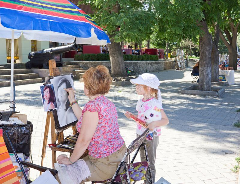 Street artist and little girl royalty free stock photo