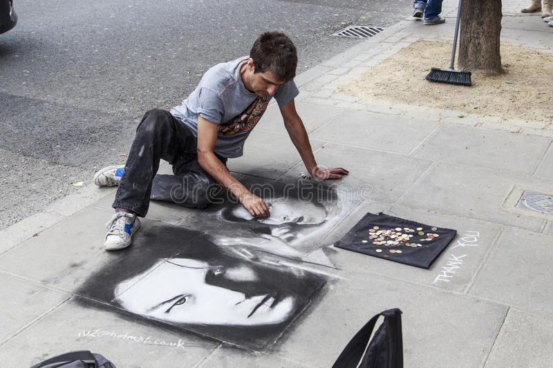 Street artist in London. LONDON, GREAT BRITAIN - MAY 17, 2014: An unidentified street artist paints on the sidewalk with chalk and charcoal royalty free stock photos