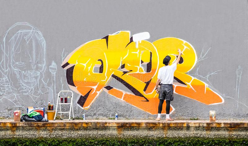 Street artist painting colored graffiti on public space wall. Modern art concept of urban guy performing and preparing live murales paint with yellow aerosol stock image