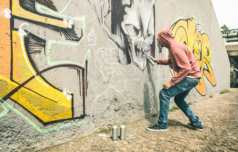 Street artist painting colorful graffiti art on generic wall royalty free stock photos